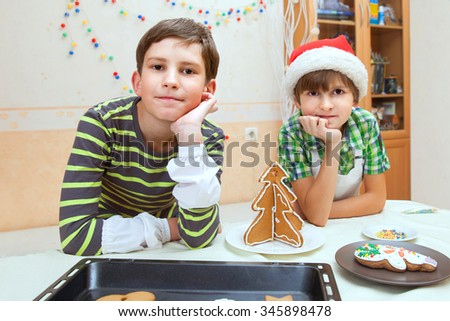 two boys cook Christmas cookies at the table