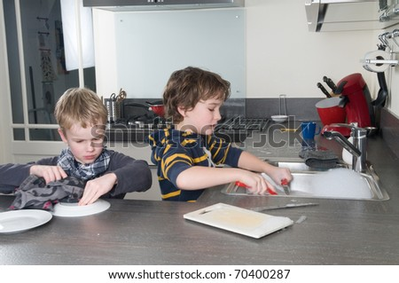 Two boys doing the dishes in a modern kitchen.