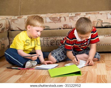 two boys draw with paints sitting on floor - stock photo