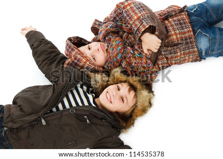 two boys dressed in winter jackets lying on snow - stock photo