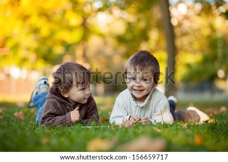 Two boys, eating cookies on the grass