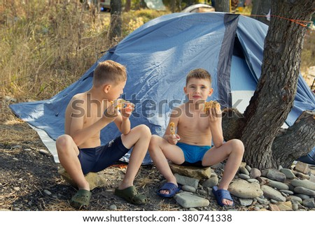 Two boys eating near tent - stock photo