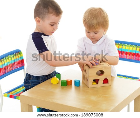 two boys enthusiastically paint markers while sitting at table. Isolated on white background. - stock photo