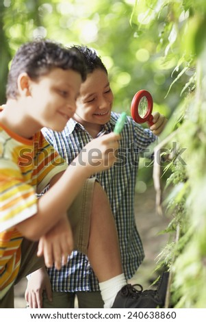 Two Boys Examining Plant with Magnifying Glass - stock photo