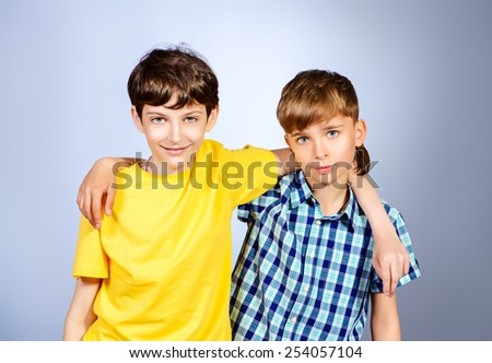 Two boys friends teenagers standing together. Studio shot. - stock photo