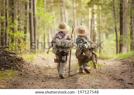 Two boys go hiking with backpacks on a forest road bright sunny day - stock photo