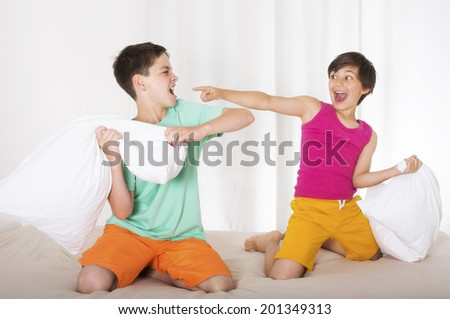 two boys having a pillow fight and laughing