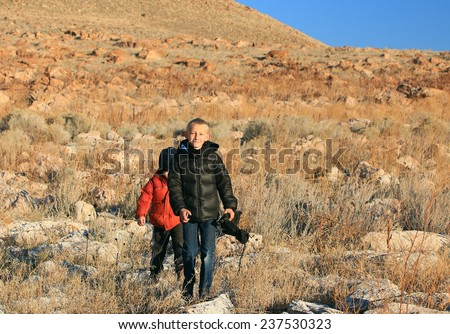 Two boys hiking in the Utah desert on a cold day.