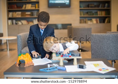 Two boys in business dress playing with toys on the table in the business center, one boy uses a puncher. - stock photo