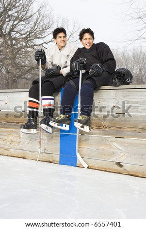 Two boys in ice hockey uniforms sitting on ice rink sidelines looking and smiling. - stock photo