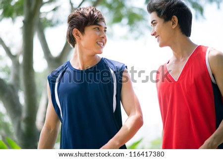 Two boys in sports clothing talking outdoors