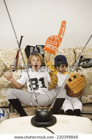 Two boys in sports gear watching television - stock photo