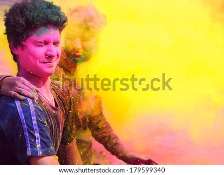 Two boys in the fog of colors/ gulal during Holi celebration in India. - stock photo