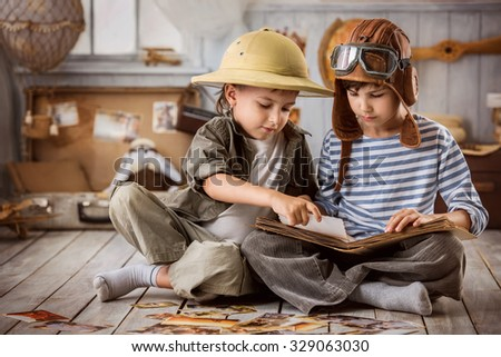 Two boys in the form of tourists and a pilot See photos from his travels - stock photo