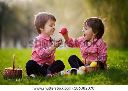 Two boys in the park, having fun with colored eggs for Easter - stock photo