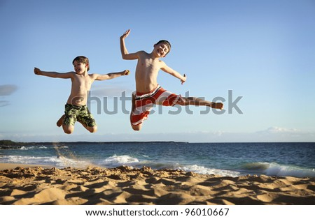 two boys jumping at the beach - stock photo