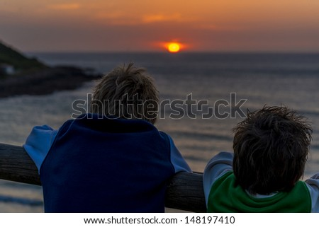 two boys looking at a beautiful sunset - stock photo