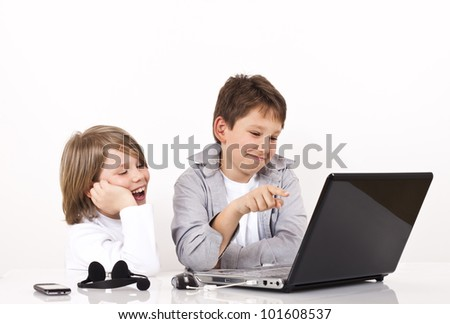 Two boys looking at something on lap top and smiling.