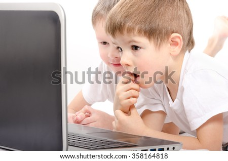Two boys looking on laptop screen, closeup, on a white background - stock photo