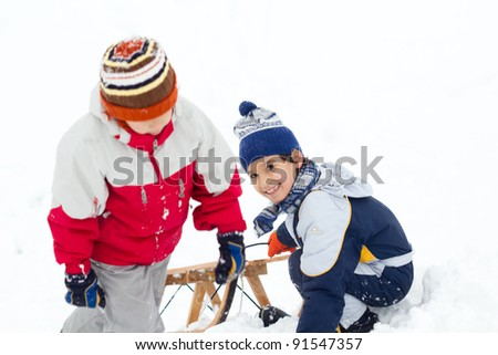two boys on the snow with sled - stock photo