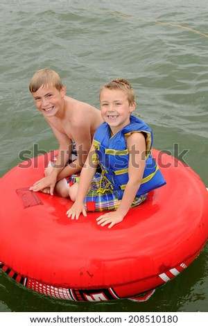 two boys on tube in lake - stock photo