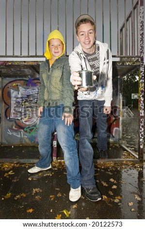 Two boys outdoors, in autumn, showing a tin can. - stock photo