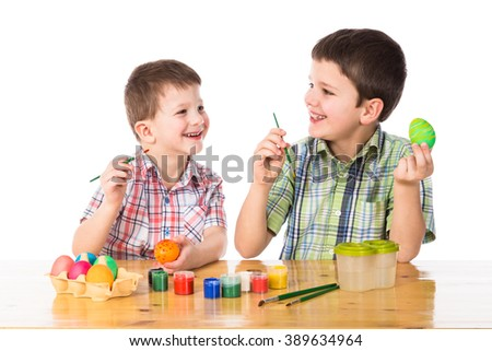 Two boys painting easter eggs, isolated on white