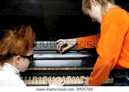 Two boys play on the piano - stock photo