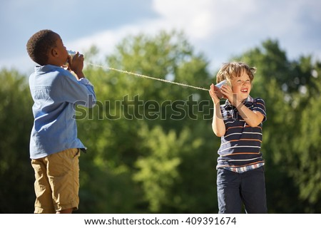 Two boys play tin can telephone with each other at the park - stock photo
