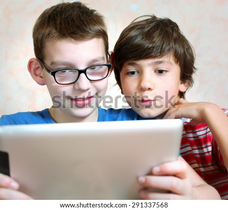 two boys play with pad computer - stock photo