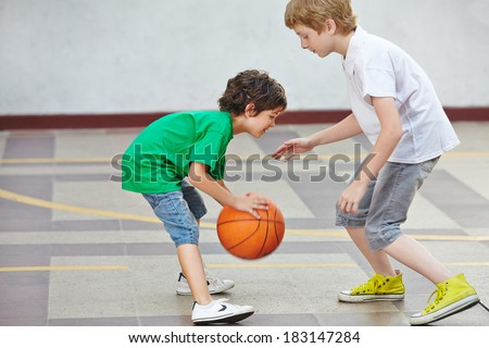Two boys playing basketball together in the schoolyard of a school - stock photo