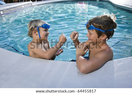 Two boys playing game of rock, scissors, paper in swimming pool, 7 and 9 years - stock photo