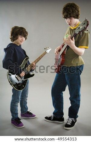 Two boys playing guitar and bass - stock photo