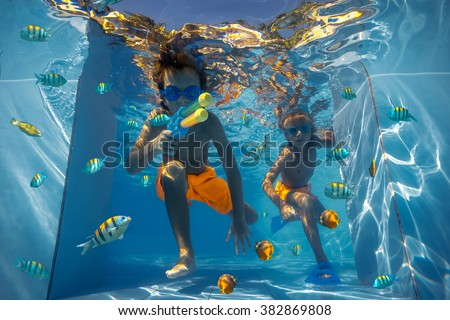 Two boys playing in the swimming pool  - stock photo