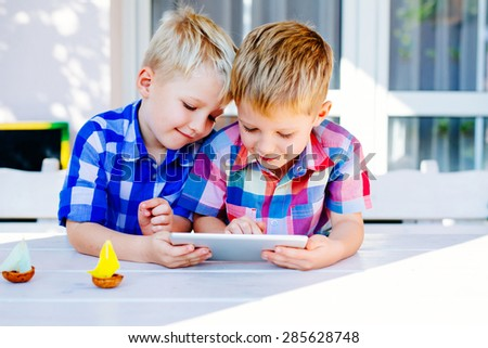 Two boys playing on digital tablet sitting outside of home