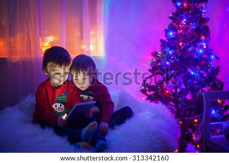 Two boys, playing on tablet at home, next to christmas tree in the evening - stock photo