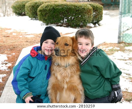 Two Boys playing outside in the Snow with the dog