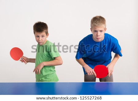 two boys playing table tennis - stock photo