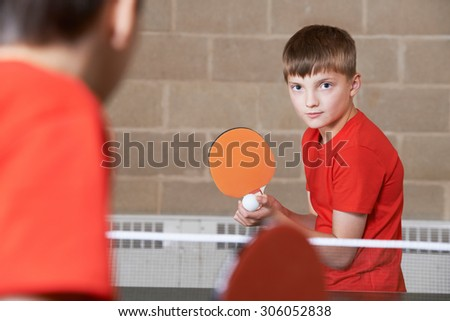 Two Boys Playing Table Tennis Match In School Gym - stock photo