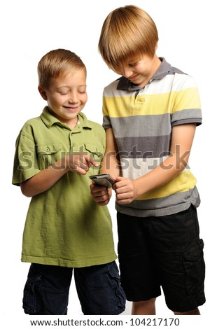 Two boys playing with a portable internet device. Nine and seven year old boys having fun with a portable internet device or handheld game console. - stock photo