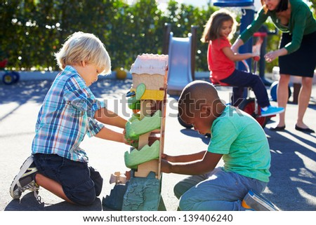 Two Boys Playing With Toy In Playground - stock photo