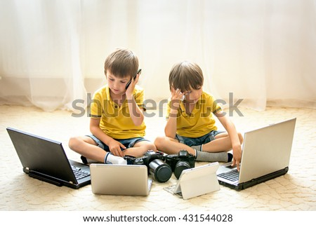 Two boys, preschool children, having fun playing at home with computers and talking on the phone - stock photo
