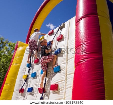 Two boys racing up balloon / inflatable climbing wall - stock photo
