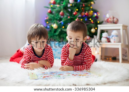 Two boys, reading a book in front of Christmas tree - stock photo