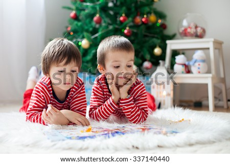 Two boys, reading a book in front of Christmas tree at home - stock photo