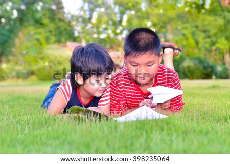 Two boys, reading a book on lawn