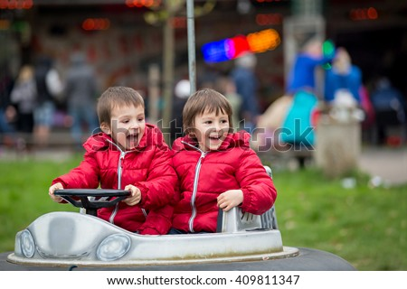 Two boys, riding boat in amusement park, having fun