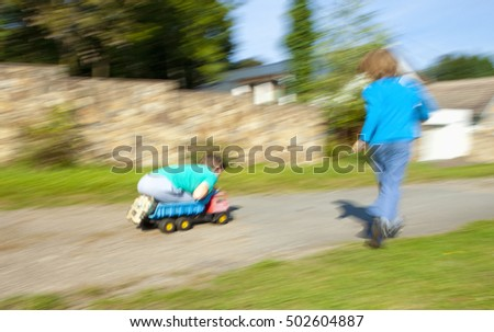 Two Boys Riding Downhill on Top of Toy Lorry