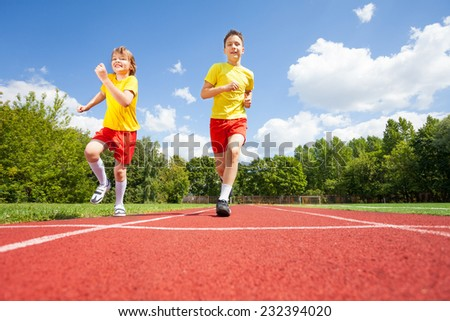 Two boys run while competing who is faster on stadium road in summer - stock photo
