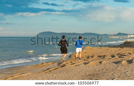Two boys running on the sand at the beach